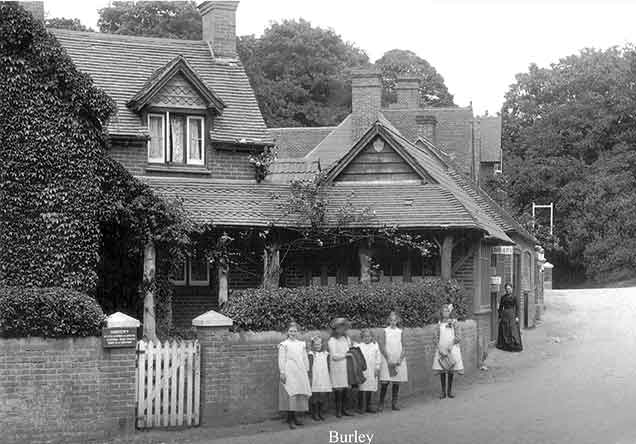 Burley - a group of young children pose for the camera outside the doctors' surgery, watched by an older lady outside the library. (Early years of the 20th century).